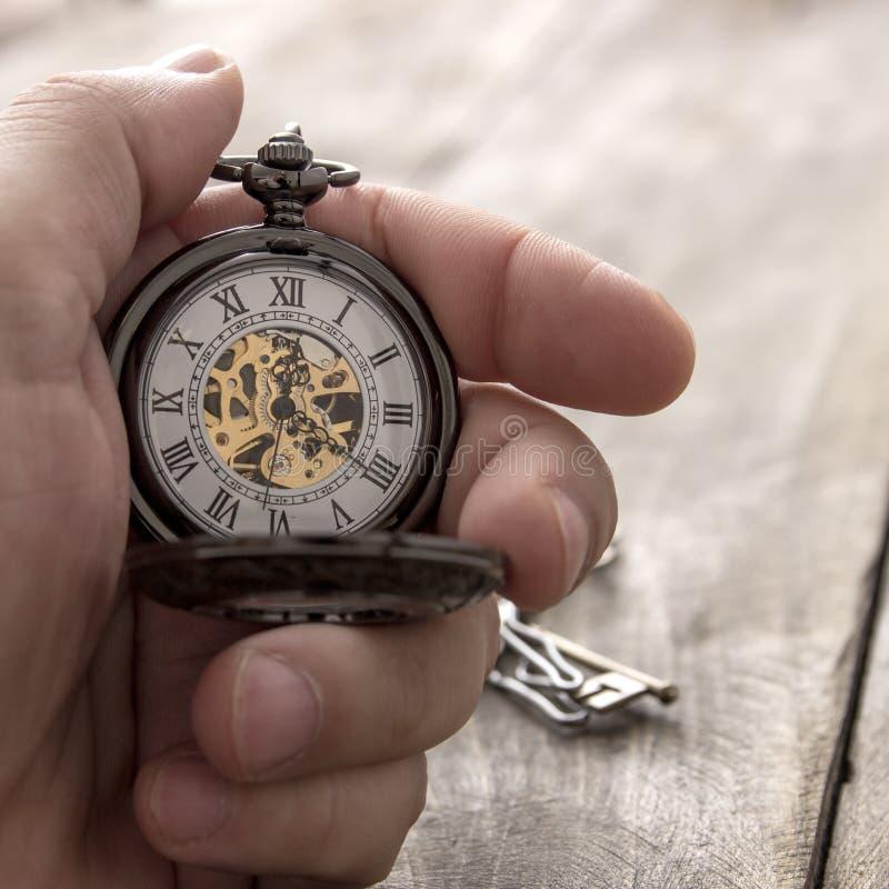 Mains avec la montre de poche de vintage photos stock