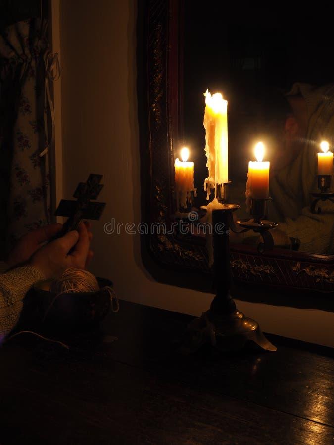Mains avec le crucifix et bougies dans l'obscurité image libre de droits