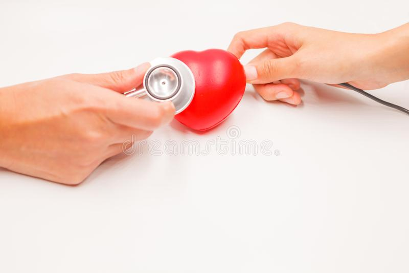 Mains avec le stéthoscope et le câble de remplissage pour vérifier et traiter le coeur sur le fond blanc Protection de maladie ca photo libre de droits