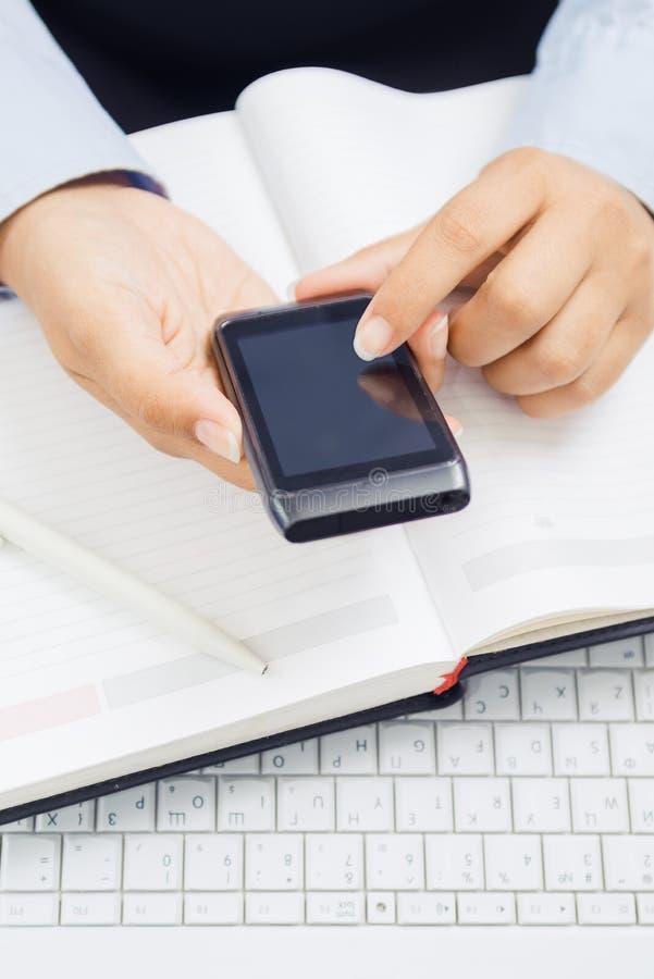 Mains avec le téléphone et l'ordinateur portable intelligents image libre de droits