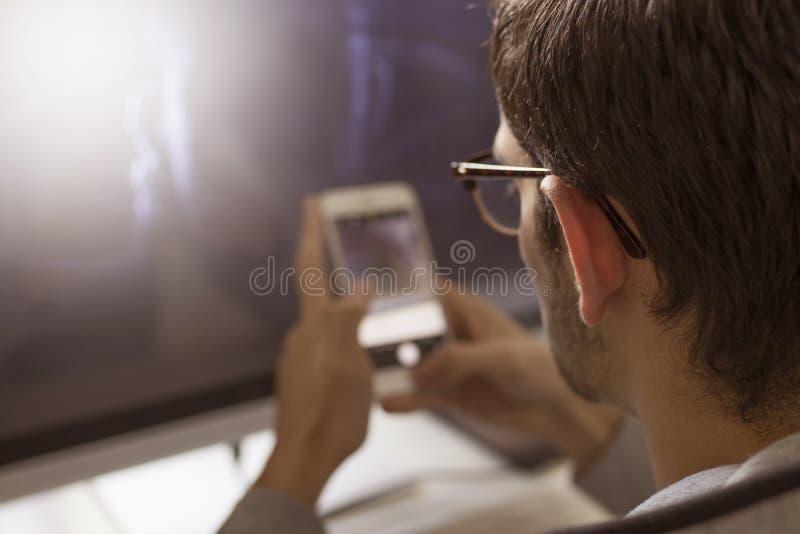 Mains avec le téléphone portable sur le bureau photo libre de droits