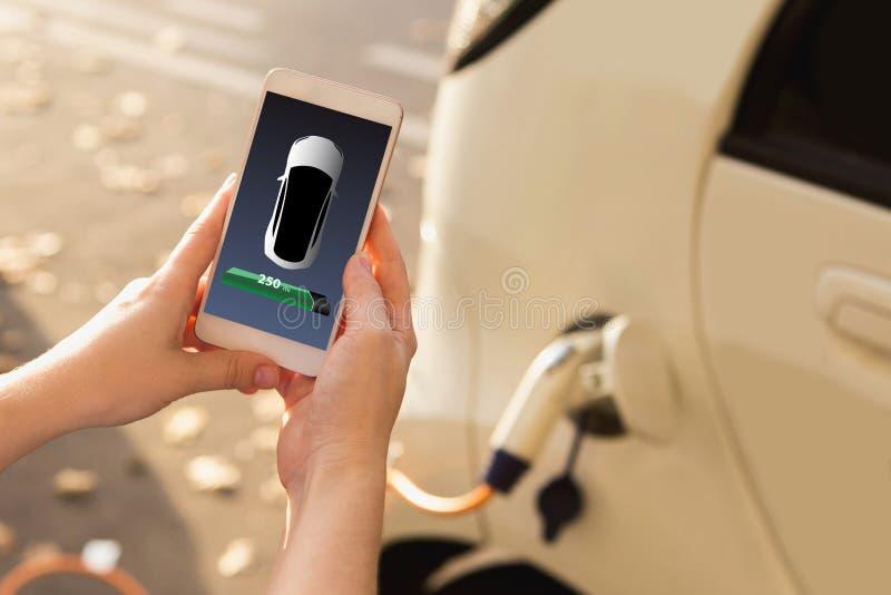 Mains avec le téléphone sur un fond de point de remplissage de voiture électrique photographie stock libre de droits