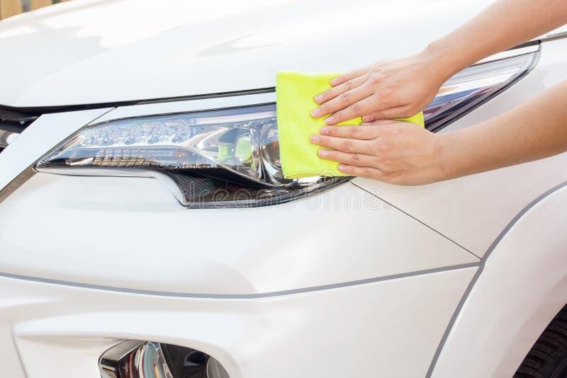 Mains avec le tissu jaune de microfiber nettoyant la grande voiture blanche photographie stock