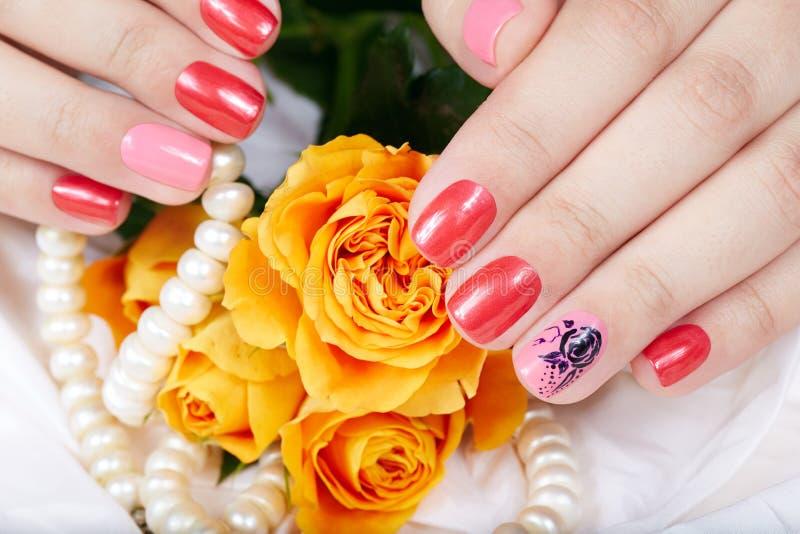 Mains avec les ongles manucurés courts colorés avec le vernis à ongles rose et rouge photo stock
