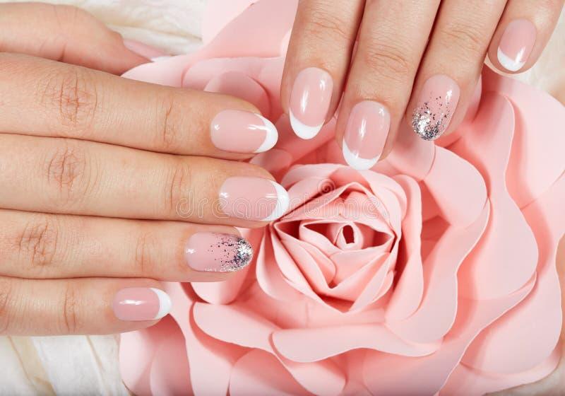 Mains avec les ongles manucurés français artificiels et la fleur rose rose image libre de droits