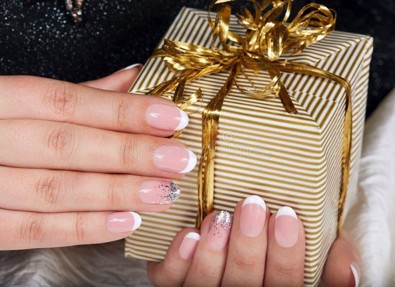 Mains avec les ongles manucurés français artificiels tenant un boîte-cadeau image libre de droits