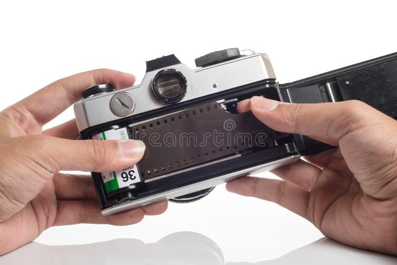Mains chargeant le film dans l'appareil-photo photographie stock
