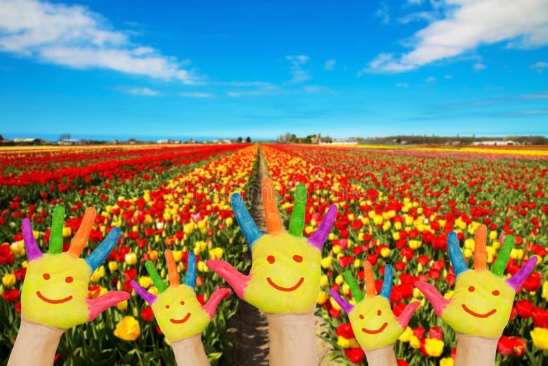 Mains colorées avec les visages peints contre des gisements de fleur photographie stock