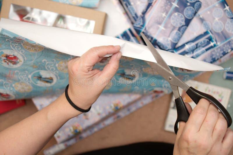 Mains coupant le papier de cadeau photo libre de droits