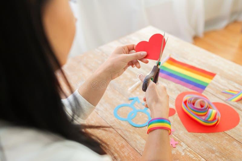 Mains coupant le ruban gai de conscience par des ciseaux photographie stock libre de droits