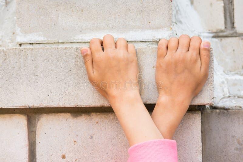 Mains croisées d'enfants saisies sur le mur de briques image stock