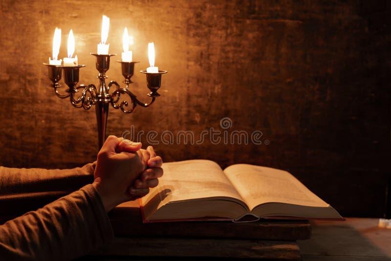 Mains crois?es femelles religieuses dans la pri?re avec la bible photos stock