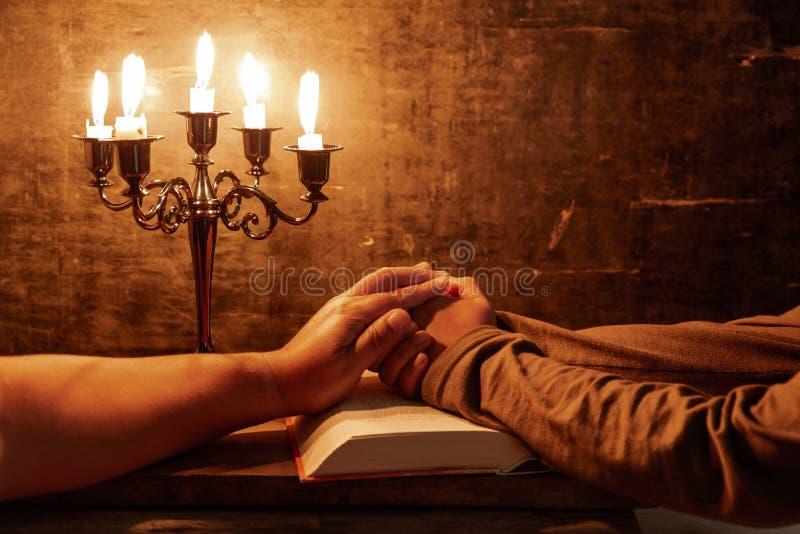 Mains crois?es femelles religieuses dans la pri?re avec la bible et la bougie images stock