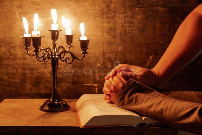 Mains crois?es femelles religieuses dans la pri?re avec la bible et la bougie image libre de droits
