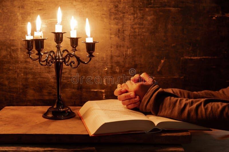 Mains crois?es femelles religieuses dans la pri?re avec la bible et la bougie images libres de droits