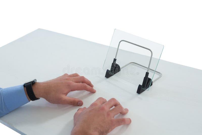 Mains cultivées d'homme d'affaires dactylographiant sur le clavier imaginaire tout en employant l'interface en verre photos stock