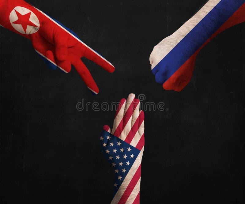 Mains décorées dans les drapeaux de la Corée du Nord, des Etats-Unis et de la Russie montrant des ciseaux, papier, pierre - les r image libre de droits