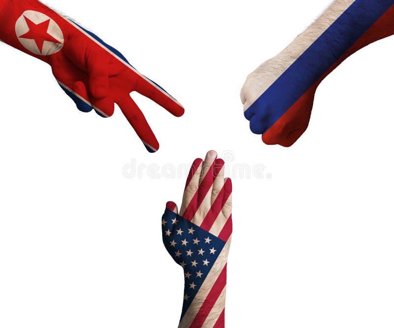 Mains décorées dans les drapeaux de la Corée du Nord, des Etats-Unis et de la Russie montrant des ciseaux, papier, pierre - symbo photos stock