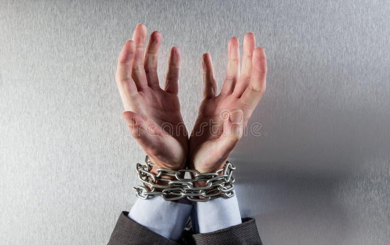 Mains désespérées d'homme attachées avec la chaîne priant pour la victime des employés photos libres de droits