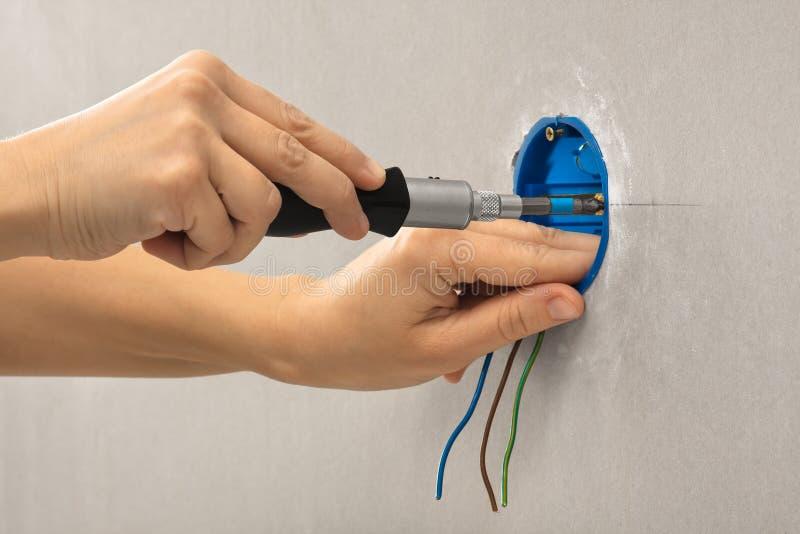 Mains d'électricien installant la boîte de débouché photo libre de droits