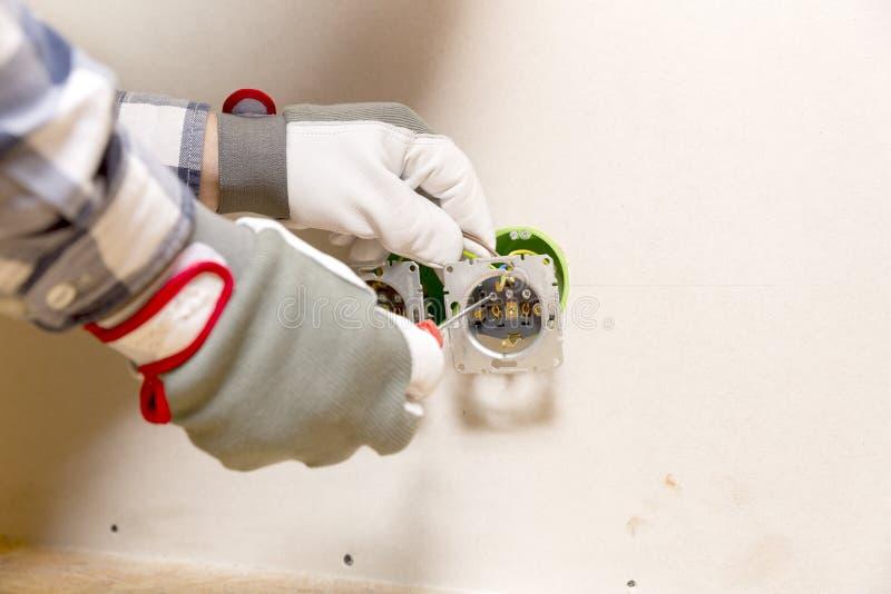 Mains d'électricien installant la prise dans le mur de gypse photographie stock