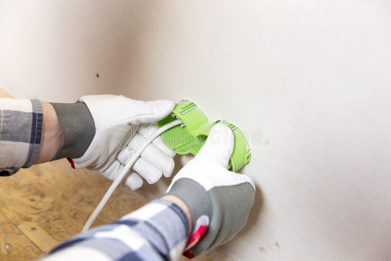 Mains d'électricien installant la prise dans le mur de gypse photo stock