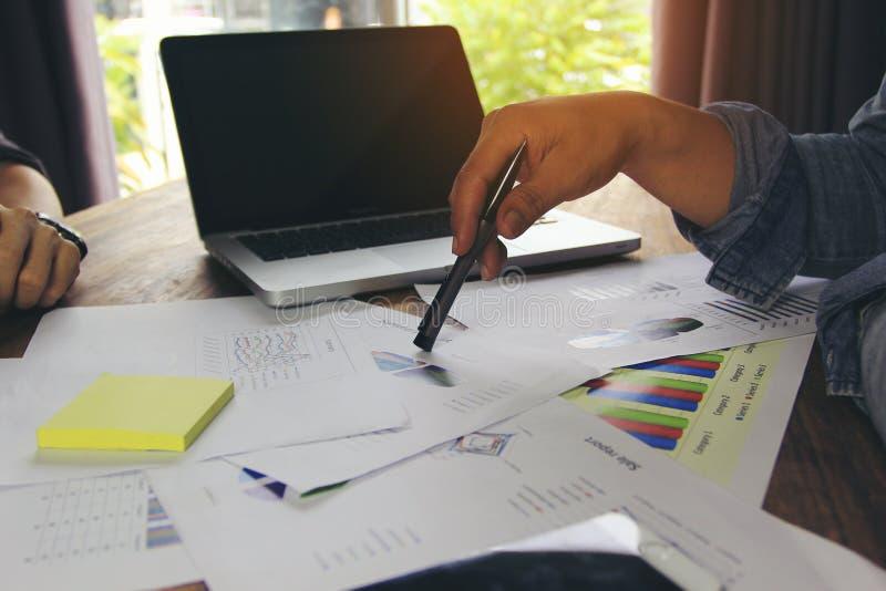 Mains d'équipe d'affaires au travail avec discuter les diagrammes et la base de données de graphiques sur la table photographie stock