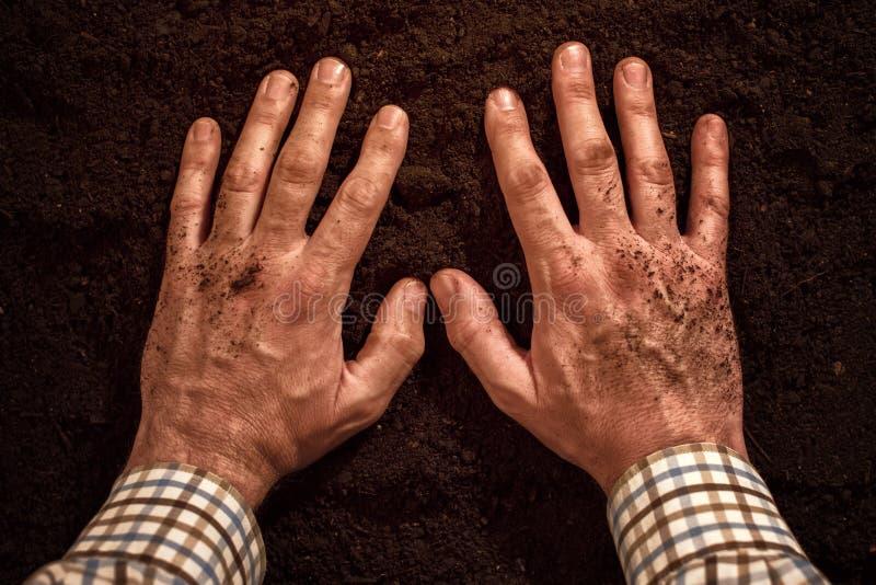 Mains d'agriculteurs sur l'au sol de sol fertile images libres de droits