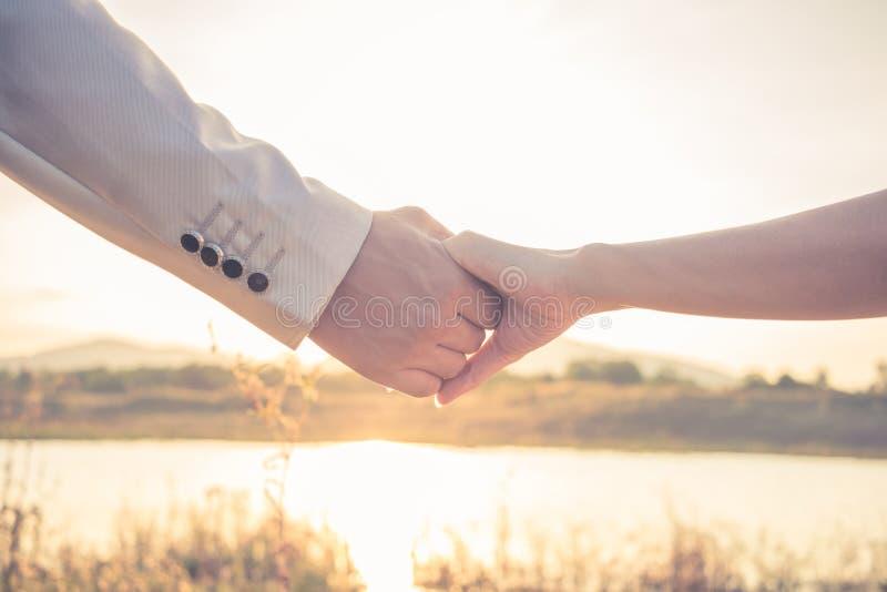 Mains d'amant au coucher du soleil photo stock