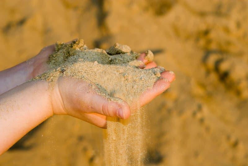 Mains d'enfant avec le sable images stock