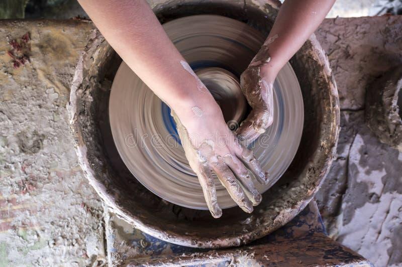 Mains d'enfant formant la cuvette sur la roue de potiers photos libres de droits
