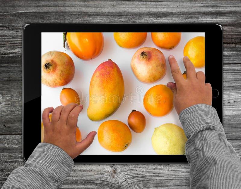 Mains d'enfant sur la tablette avec la photo mélangée de fruit image stock