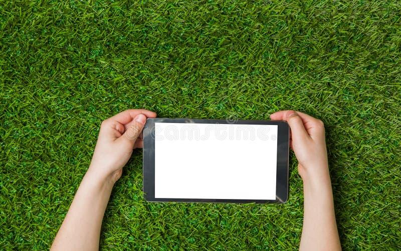 Mains d'enfant tenant le PC de comprimé au-dessus de l'herbe verte photos libres de droits