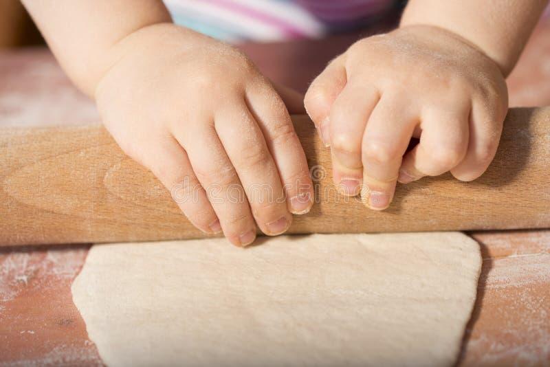 Mains d'enfants malaxant la pâte photographie stock