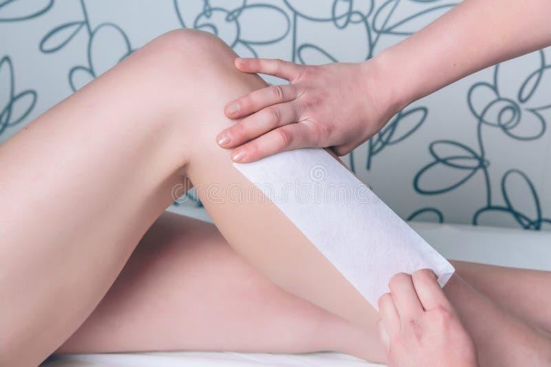 Mains d'esthéticien faisant le dépilage chez des jambes de la femme photo stock