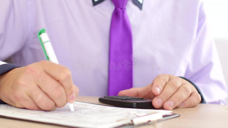 Mains d'homme d'affaires avec les papiers de calculatrice et d'écriture et de classement de stylo ou la feuille d'impôt  photo stock