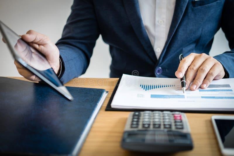 Mains d'homme d'affaires utilisant l'information des textes sur le comprimé numérique pour analyser des données statistiques fina photographie stock libre de droits