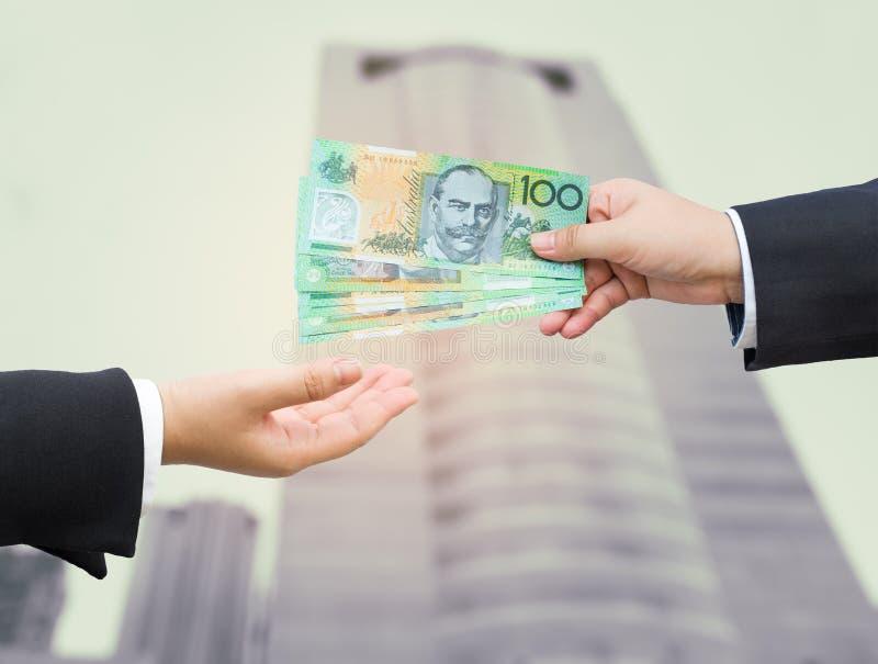 Mains d'homme d'affaires passant le billet de banque du dollar australien (AUD) photographie stock