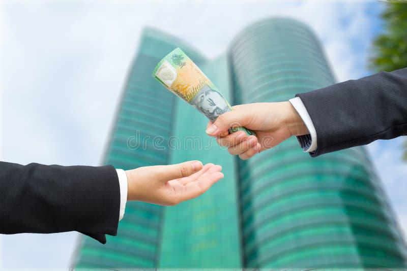 Mains d'homme d'affaires passant le billet de banque du dollar australien (AUD) photos stock