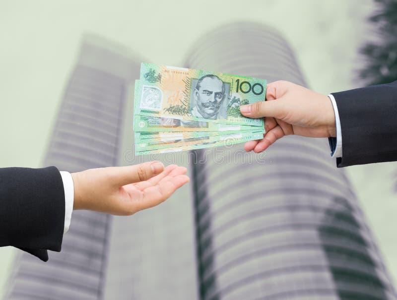 Mains d'homme d'affaires passant le billet de banque du dollar australien (AUD) photographie stock libre de droits