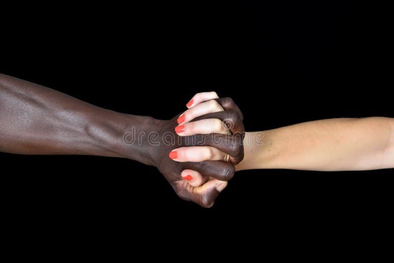 Mains d'homme de couleur et de femme blanche sur le noir images stock