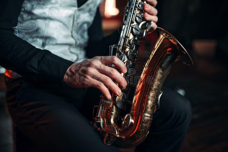 Mains d'homme de jazz tenant le plan rapproché de saxophone photo stock