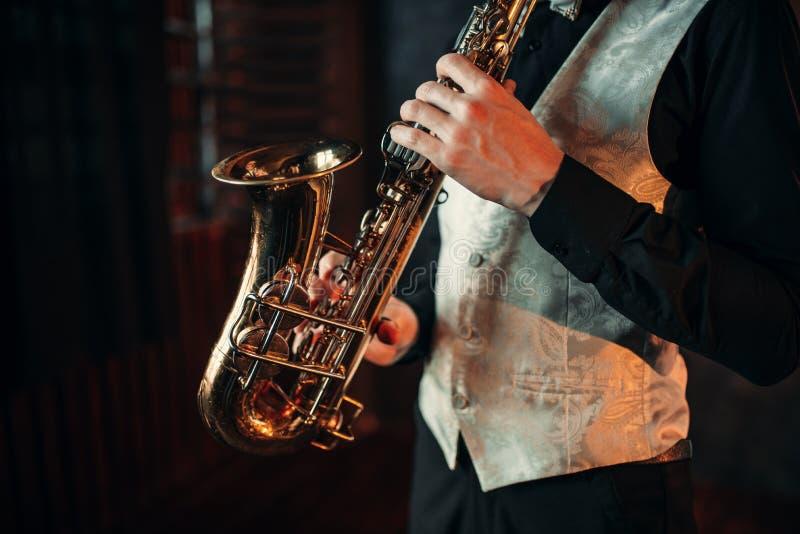 Mains d'homme de jazz tenant le plan rapproché de saxophone image libre de droits
