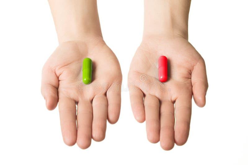Mains d'homme donnant deux grandes pilules Vert et rouge Faites votre sélection mode de vie ou mauvaises habitudes sain Choisisse photos stock