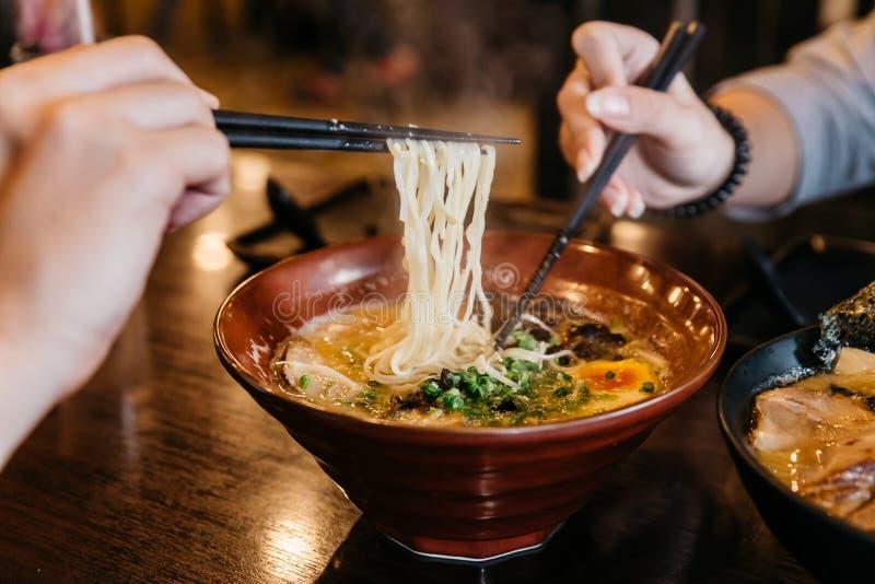 Mains d'homme et de femme pinçant la nouille en Ramen de Tonkotsu de soupe à os de porc de Ramen avec du porc de Chashu, oignon b photo stock