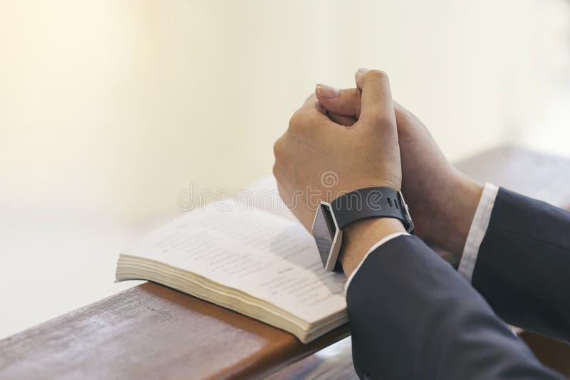 Mains d'homme priant sur une Sainte Bible dans l'église pour le concept de foi, la spiritualité et la religion chrétienne image libre de droits