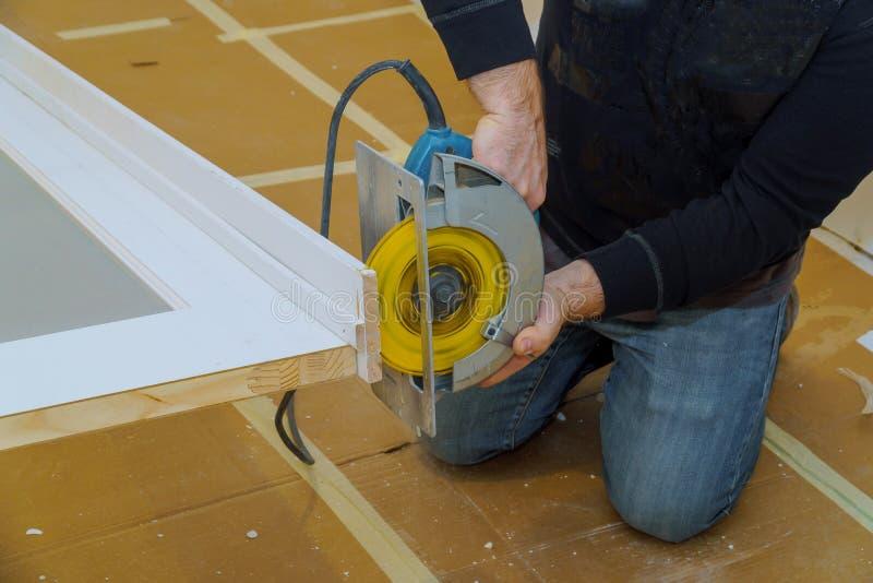Mains d'homme tenant la scie circulaire et préparant pour faire une coupe dans la porte images libres de droits