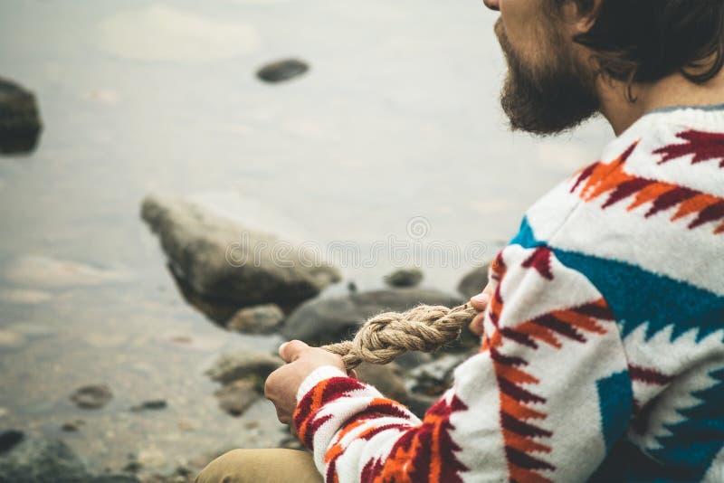Mains d'homme tenant la survie de mode de vie de voyage de noeud de corde photos libres de droits