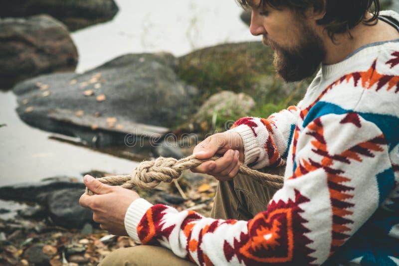Mains d'homme tenant la survie de mode de vie de voyage de noeud de corde image stock