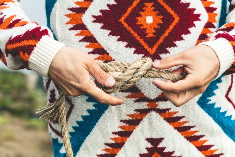 Mains d'homme tenant le mode de vie de voyage de noeud de corde photographie stock libre de droits
